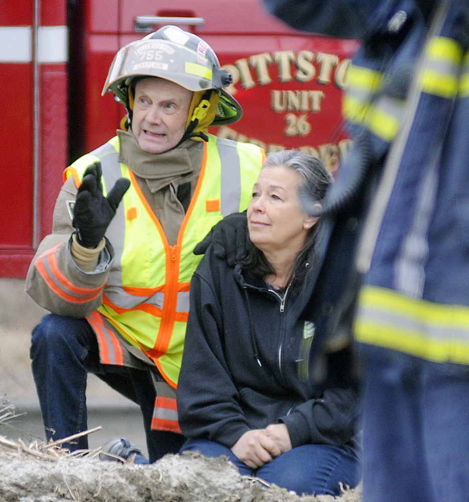 Hallowell Fire Department Chaplain Peter Inchombe comforts Grace Montalbo Wednesday as firefighters battle a blaze at her Farmingdale home.