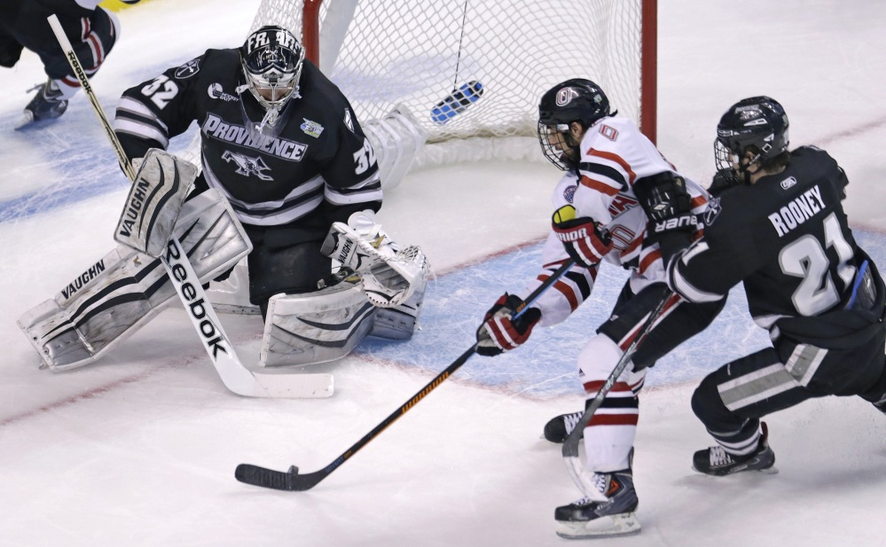 Providence goalie and South Portland native Jon Gillies, left, follows the puck as Omaha forward Tyler Vesel, center, tries for a back-hander during the first period Thursday of their semifinal game at the NCAA Frozen Four in Boston. At right is Providence forward Kevin Rooney.