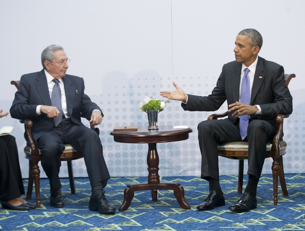 U.S. President Barack Obama, right, extends his hand towards Cuban President Raul Castro, left, to shake hands during their meeting at the Summit of the Americas, in Panama City, Panama, Saturday.