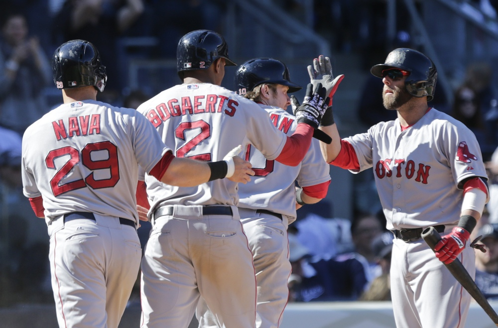 Boston Red Sox's Dustin Pedroia, right, celebrates with teammates Daniel Nava, 29, Xander Bogaerts, 2, and Ryan Hanigan, 10, after they scored on a double by Brock Holt during the eighth inning of a baseball game Saturday in New York.