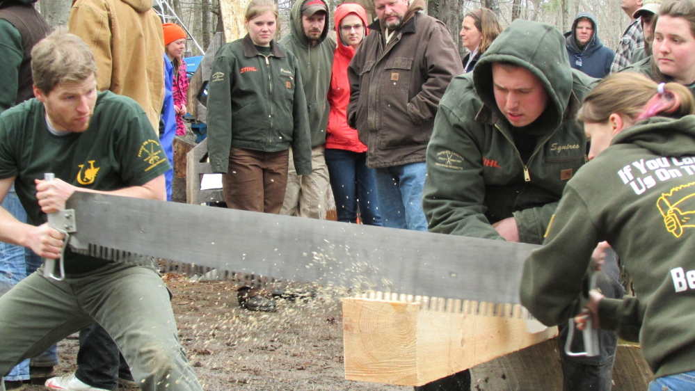 Unity College students Joe Ranzoni and Lauren Souther saw through a beam at the annual Mud Meet collegiate woodsmen competition at Colby College in Waterville Saturday afternoon. Holding the beam is Unity student Matt Squires.