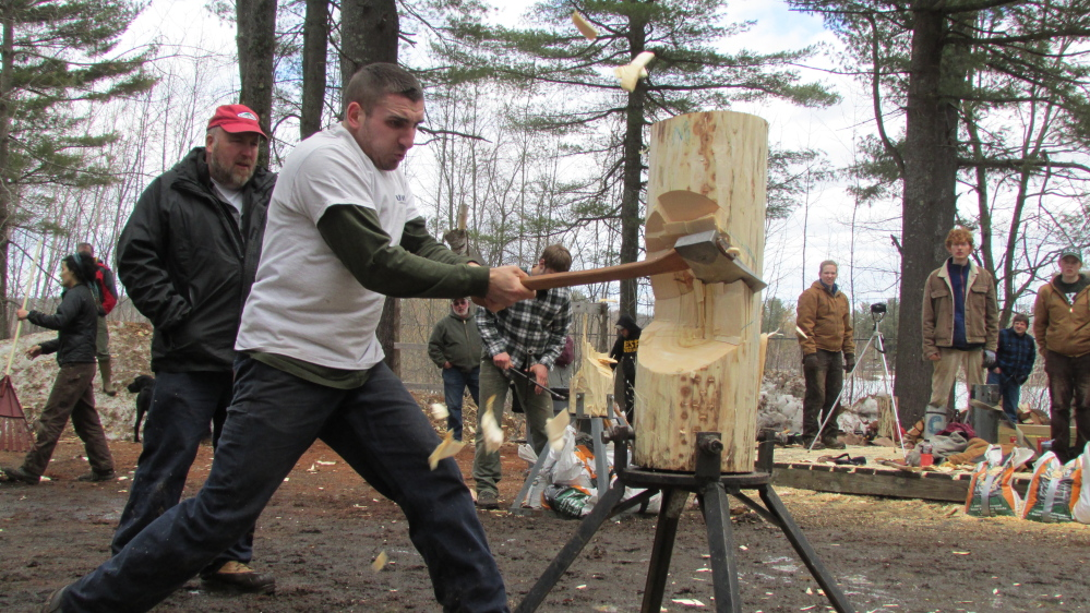 """University of New Hampshire student Mitch Andrea hacks into a log during the vertical chop event at the annual """"Mud Meet"""" woodsmen competition at Colby College in Waterville Saturday afternoon."""