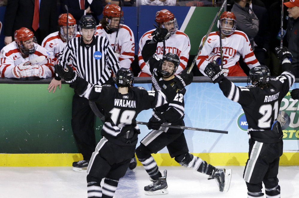 Providence forward Brandon Tanev (22) celebrates with teammates Jake Walman (19) and Kevin Rooney (21) after his go-ahead goal against Boston University during the third period Saturday of the NCAA men's Frozen Four hockey championship game in Boston. Providnece won 4-3.