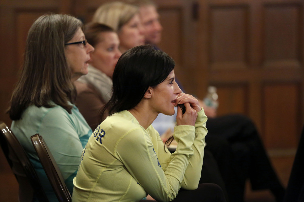 Boston Marathon bombing survivor Lynn Crisci, of Boston, listens during a Massachusetts Resiliency Center meeting at the Old South Church, in Boston. Crisci, who was near an explosion at the finish line of the 2013 Boston Marathon, has suffered from hearing loss, traumatic brain injury, and post-traumatic stress disorder
