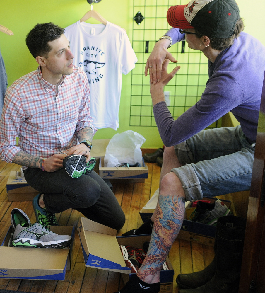 Seth Hasty helps Julia McDonald try on a pair of running sneakers at Granite City Running in Hallowell on Sunday. The store is closing after four months of helping local runners find footwear.