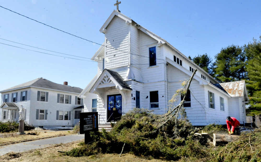 Robert Searles cuts up a tree he cut down beside St. Bridget's church in Vassalboro on Sunday. Rachel and James Kilbride bought the closed church and rectory, left, and plan to restore the buildings and open them as an event hall and community center.