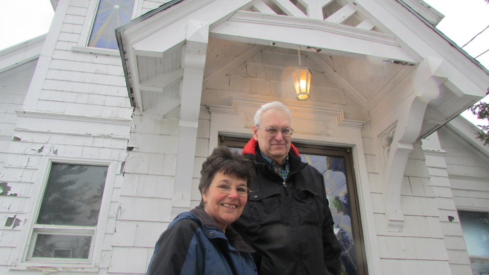 Rachel and James Kilbride stand in front of St. Bridget's church on Main Street in North Vassalboro. The couple bought the disused church in January and plan to restore and reopen it as an event and community space.