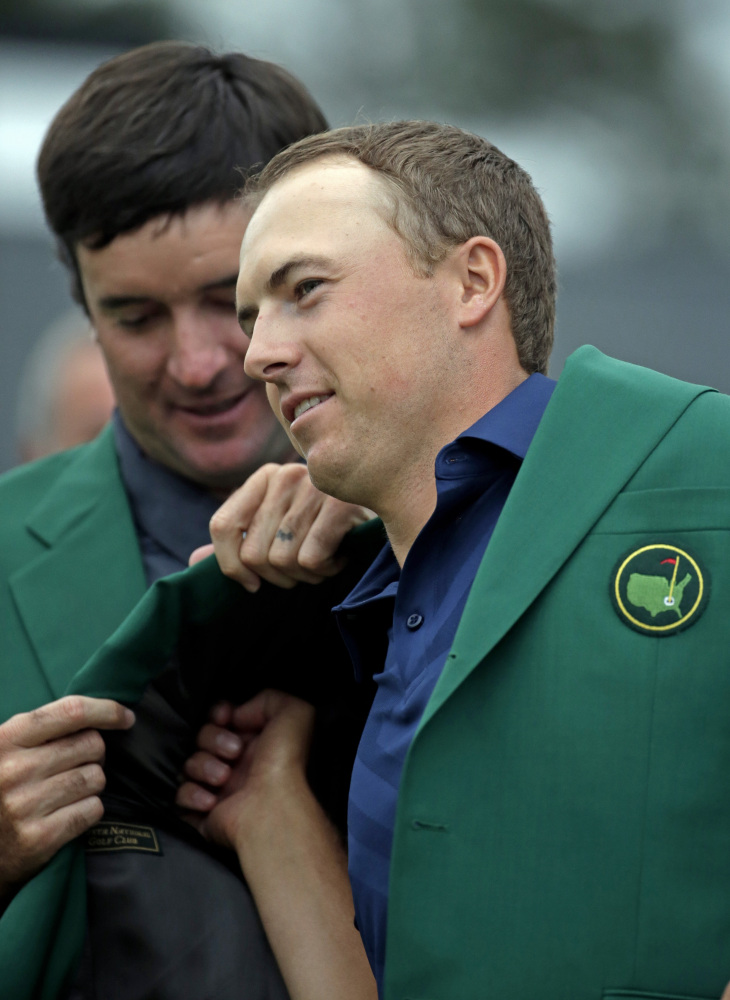 Bubba Watson helps Jordan Spieth put on his green jacket after Spieth won the Masters on Sunday in Augusta, Ga.