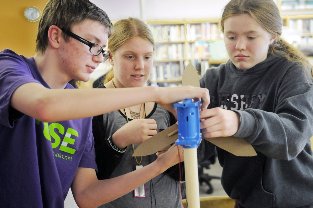 Gardiner Area High School students Graesyn Woiccak, left, Alyssa Barnes and Samantha Deans assemble a turbine Monday as part of the green technology program at the school called FUSE. The 14-year-olds explored hands-on challenges inspired by real-world green technology as part of the FUSE program.