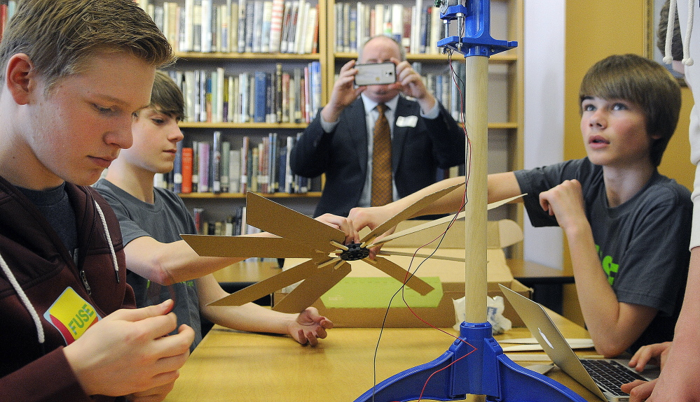 Tom Desjardin, acting commissioner of the Maine Department of Education, photographs Gardiner Area High School students assembling a wind turbine Monday as part of the green technology program at the school called FUSE.