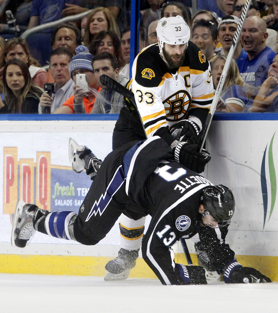 Tampa Bay Lightning center Cedric Paquette (13) goes down after Boston Bruins defenseman Zdeno Chara (33) fights off a check during the second period Saturday in Tampa, Fla.