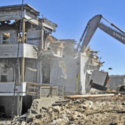 Debris flies as an excavator operator demolishes 15 State St. in Augusta on Tuesday.