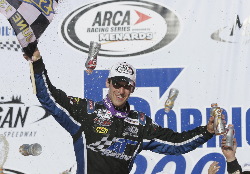 Fort Kent driver Austin Theriault holds the checkered flag after winning the ARCA Corrigan Oil 200 at Michigan International Speedway in Brooklyn, Mich. on June 13, 2014.