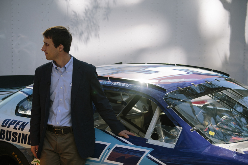 Austin Theriault poses by his Maine-branded race car following a press conference in Portland last September.