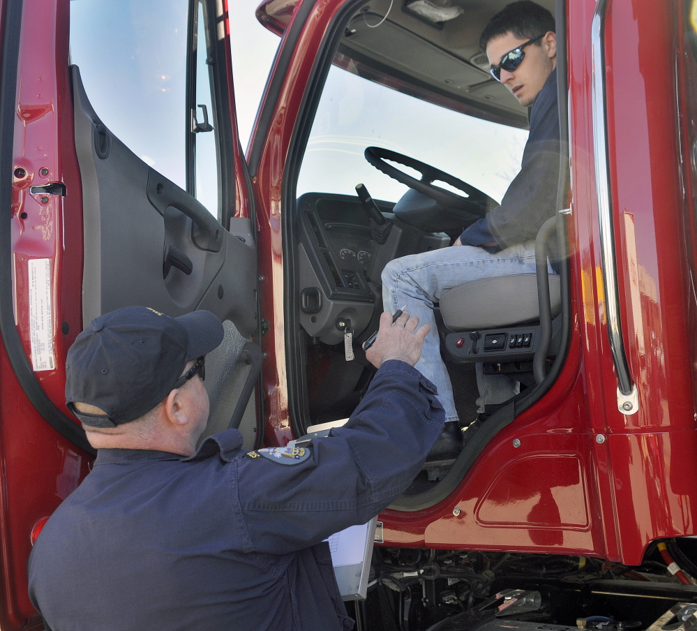 Parker Gardner, 17, of Lincoln, inspects a dump truck Wednesday with State Trooper Chris Foxworthy during the Dick Dolloff Memorial Student Driving Competition at the Augusta Civic Center. Students from across Maine competed in the event to test the skills of high school tractor-trailer operators. Troopers with the truck weight division tested teenagers on their knowledge of truck safety.