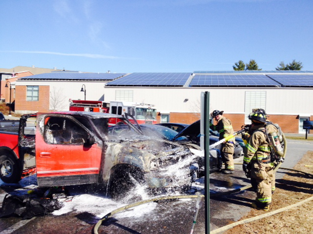 Waterville firefighters hose down a pick-up truck that burst into flames shortly after a Thomas College student parked it in a school parking lot Thursday morning.