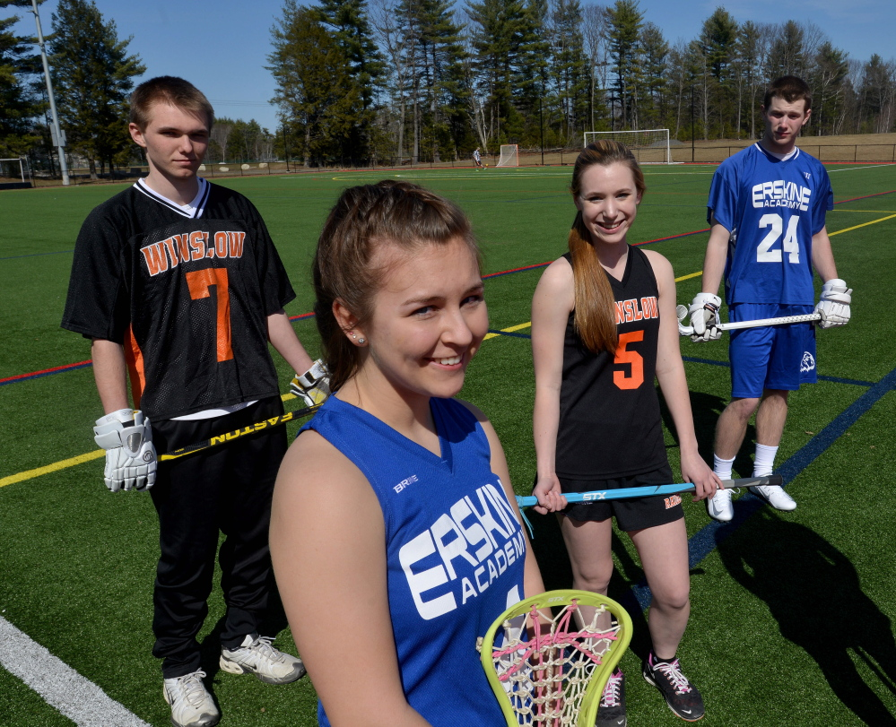 Erskine's Kiley Drummond, foreground, stands with Winslow High School's Jimmy Fowler, back left, Cassidy Roderick, back center, and Erskine classmate Trever Browne, back right, at Thomas College in Waterville on Thursday. Erskine and Winslow will field varsity girls and boys lacrosse teams for the first time this spring.
