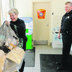 Carmen McCurdy, left, chats with Gardiner Police Sgt. Todd Pillsbury as she drops of medicine during the annual drug take-back at the Gardiner police station in 2013. Sheriff departments across Maine are helping take over the event after the national Drug Enforcement Agency said it can no longer afford to do it.