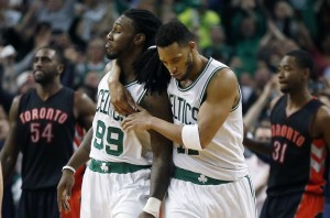 Boston Celtics' Jae Crowder (99) celebrates his basket with teammate Evan Turner in front of Toronto Raptors' Patrick Patterson (54) and Terrence Ross (31) during the final seconds of the fourth quarter Tuesday in Boston.
