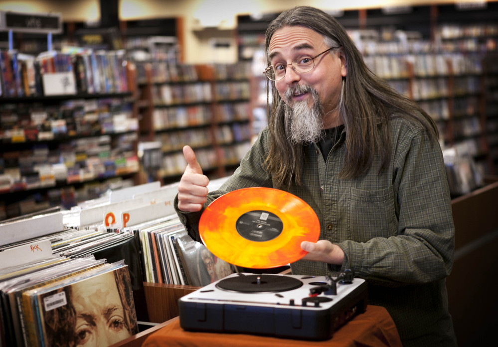 """Chris Bown poses in Scarborough with a copy of The Knack's """"Live in Los Angeles 1978.""""  Brown from Maine-based Bull Moose music hatched the idea for the annual event to celebrate local record stores, and the first one was held seven years ago."""
