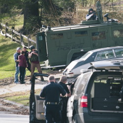 Police with an armored vehicle surround a woman after she left a house on Elizabeth Road in Portland, where a shooting on Friday left one person wounded and another in custody.