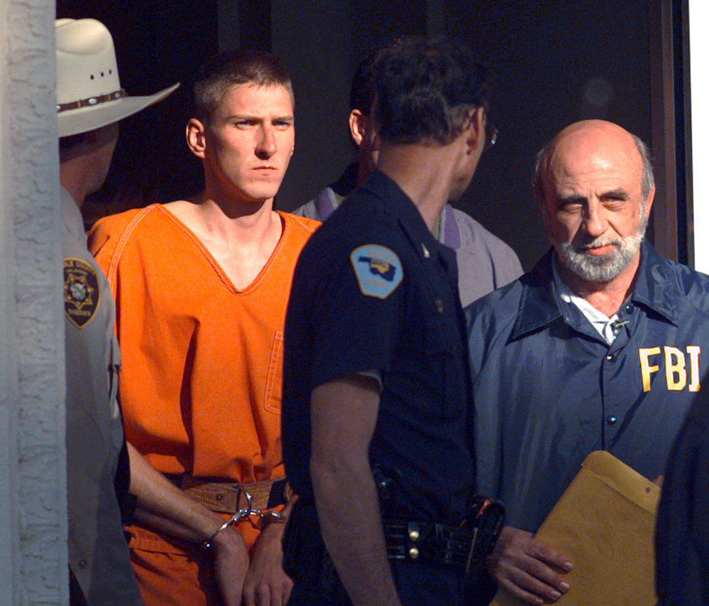 In this April 21, 1995 file photo, Timothy James McVeigh is lead out of the Noble County Courthouse by state and federal law enforcement officials in Perry, Okla., after being identified as a suspect in the bombing of the Oklahoma City Federal building.
