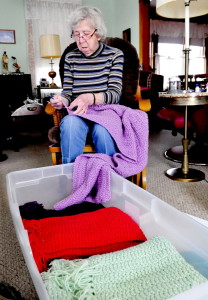 Sitting behind a container full of finished shawls at her home in Waterville, Lillian Tulley, 91, works on her latest shawl that she makes for comfort and warmth of patients dealing with cancer. Tulley said she has made 91 in the last three years.