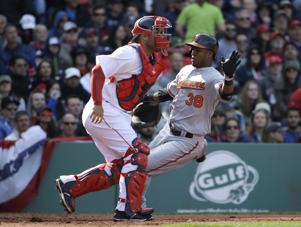 Baltimore Orioles' Jimmy Paredes, right, scores on a three-run double by teammate Adam Jones as Boston Red Sox catcher Sandy Leon, left, waits for the ball in the sixth inning of a baseball game Sunday in Boston.