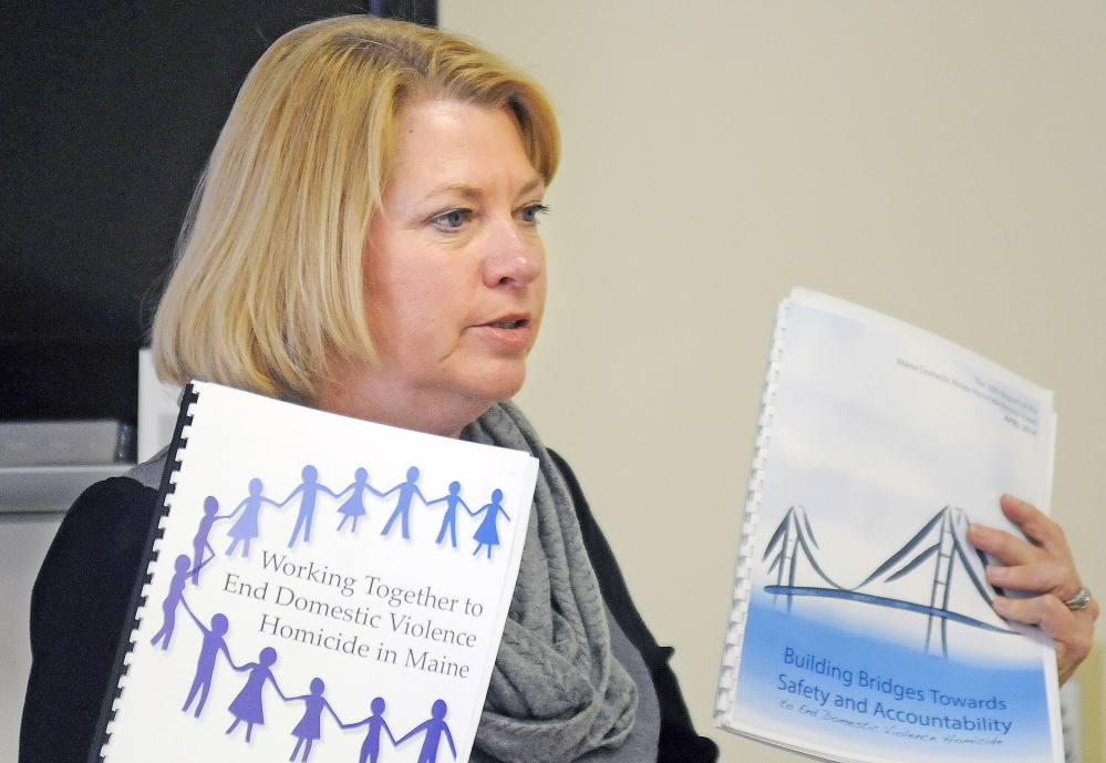 Deputy Attorney General Lisa Marchese Sunday displays two copies of the Maine Domestic Abuse Homicide Review Panel while addressing guests at the annual meeting of he Maine Chapter of Parents of Murdered Children in Augusta.