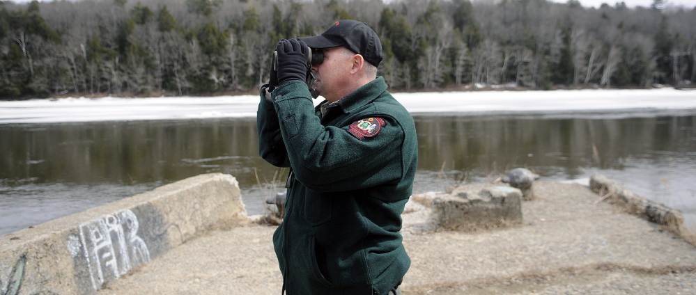 Marine Patrol Officer Clint Thompson scans the Kennebec River in Hallowell April 8 while searching for the remains of Kelly Voytasko, 54, of Augusta, who reportedly went under the ice in Augusta on March 21.