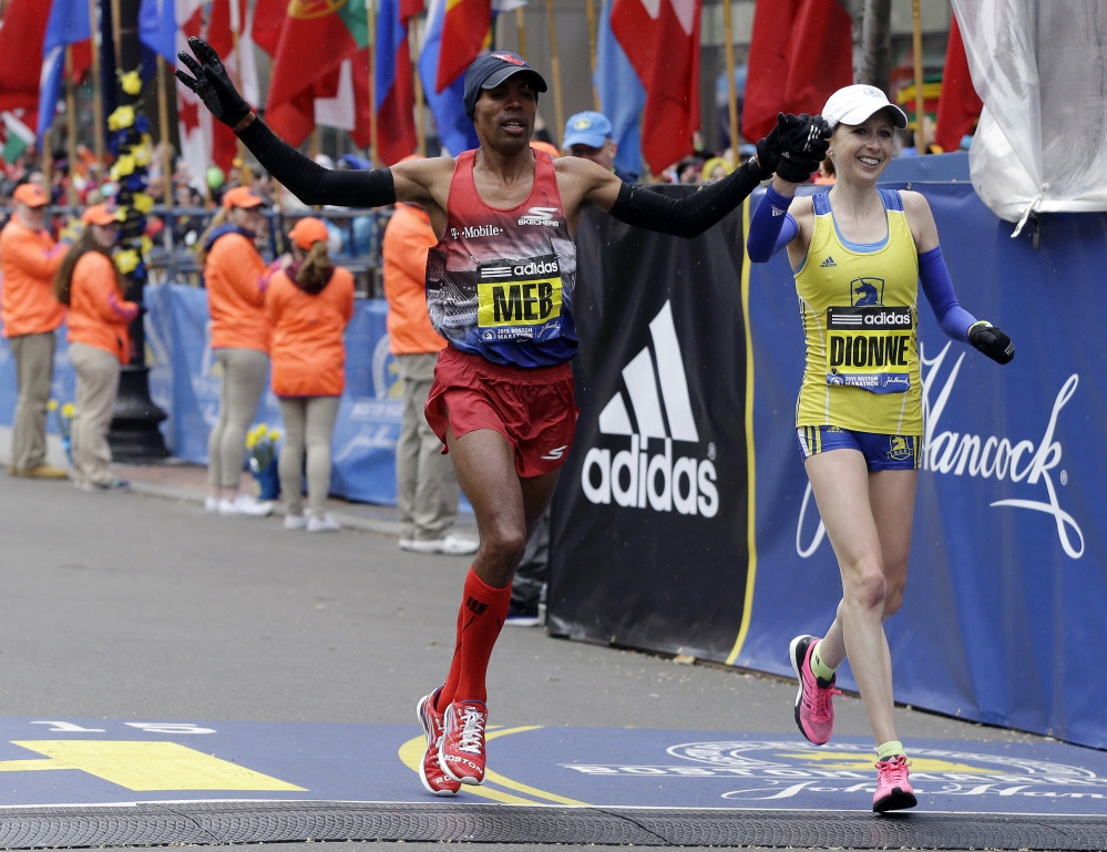 Meb Keflezighi, left, and Hilary Dionne finish the Boston Marathon on Monday. Should Boston host the Olympics in 2024, the historic course will not be able to host a marathon, as it does not meet IAAF certification.
