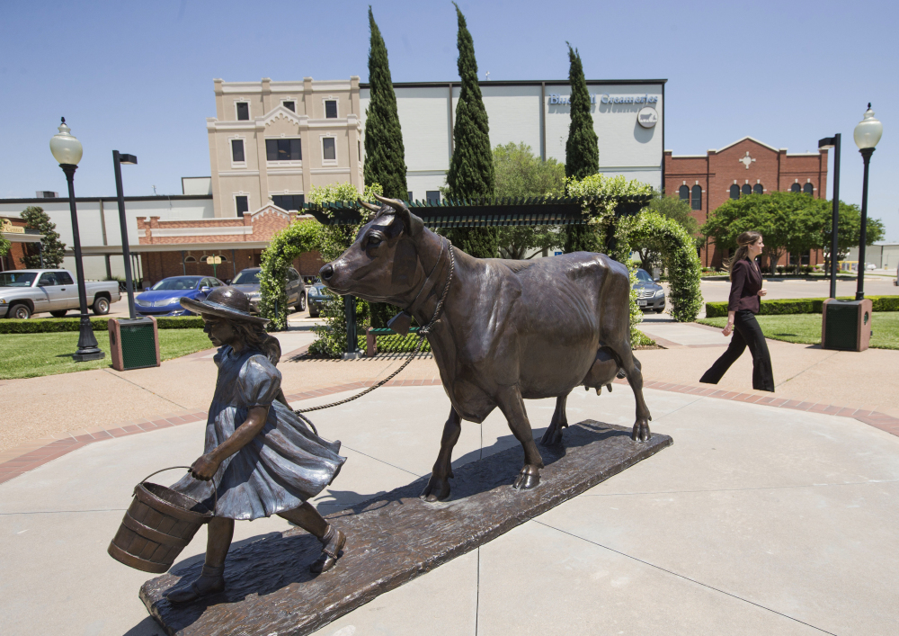 A woman walks by the Blue Bell Creameries on Tuesday, in Brenham, Texas.