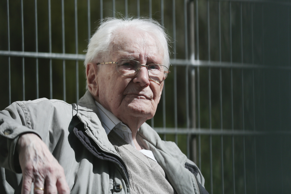 Former SS guard Oskar Groening sits in ths sun during the noon break of the trial against him in Lueneburg, northern Germany, Tuesday.