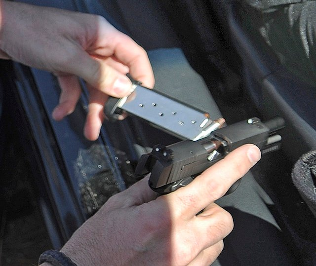 State Trooper Chris Rogers unloads a pistol recovered Wednesday from a vehicle he stopped on Interstate 95 in West Gardiner after a couple reported having a gun drawn on them while traveling in the southbound lane.
