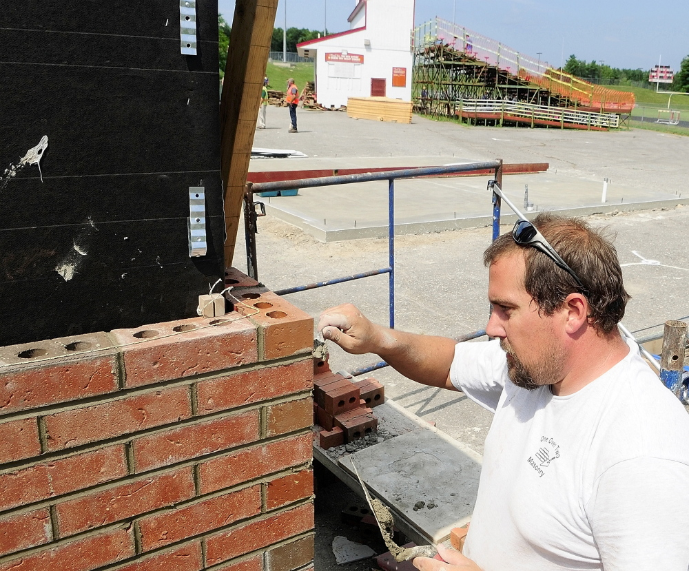 Fred Scannell, of One Over Two Masonry, mortars the joints in the brick veneer on new ticket booths at the entrance to Alumni Field at Cony High School in Augusta in 2011. The Elsie and William Viles Foundation is donating $250,000 to continue improving Alumni Field.