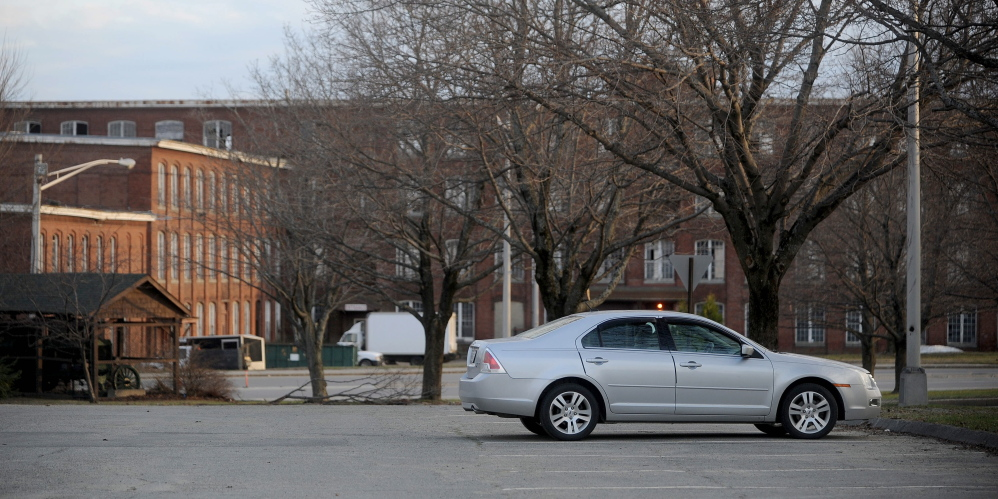 City parking lot on Front Street in Waterville is empty in the evening hours on Wednesday, and the Hathaway Creative Center is seen in the background, about a quarter-mile away. The city rejected an offer Tuesday from Hathaway developer Paul Boghossian to lease the lot to meet bank requirements for parking in order to finance the next phase of the mill rehabilitation.