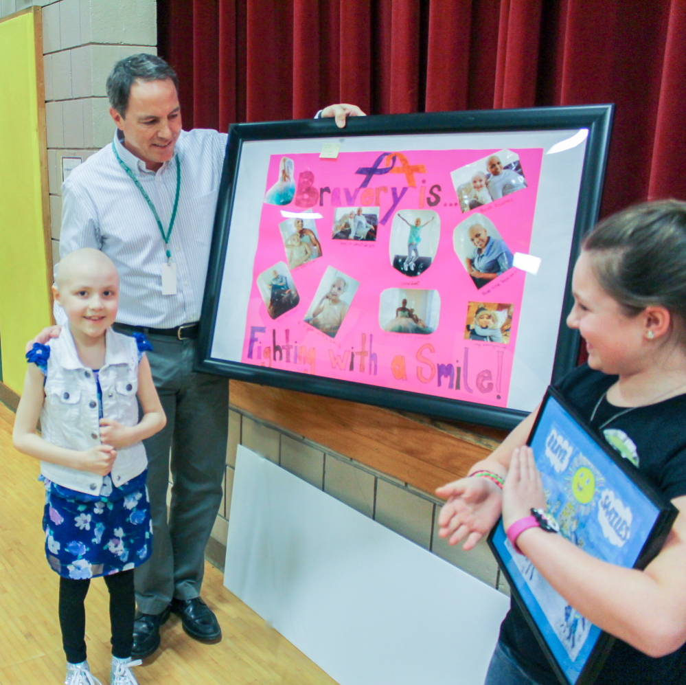 Farrington Elementary School second-grader Kendall Dorr, left, placed first in category K-3rd grade and won $500. Kristen Merrill, right, took second place in category 4th-6th grade and won $250). She is a 4th grader at Farrington Elementary School. In the center is Dr. Randall Cutri.