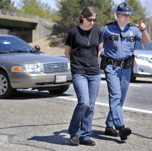 Demitria Buhalis is escorted by State Police Sgt. Patrick Hood to a cruiser Wednesday while being arrested on Interstate 95 in West Gardiner after a driver in the southbound lane reported a woman pointing a gun.