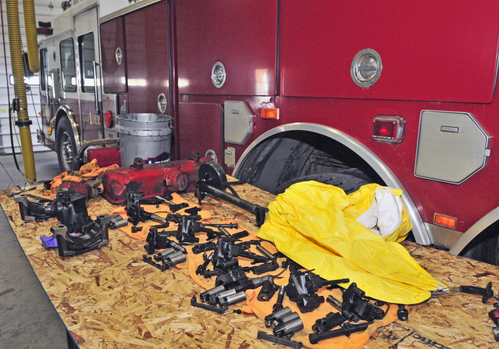 Engine parts are piled on a table Friday beside Augusta Fire Department's disabled ladder truck, which is parked in the Western Avenue station.