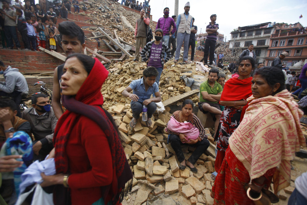 People rest on debris at Durbar Square after an earthquake in Kathmandu, Nepal, on Saturday.
