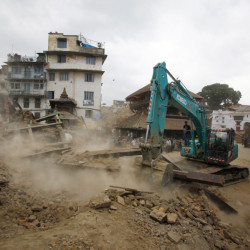 A crane removes debris from the site of a building that collapsed in an earthquake in Kathmandu, Nepal, on Saturday.