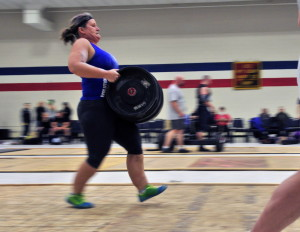 Chele Fuller runs with a keg during the carry medley Saturday at the Central Maine Strongman 8.