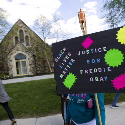 Demonstrators hold up signs outside the funeral home during Freddie Gray's wake in Baltimore, Md., on Sunday. Gray died from spinal injuries a week after he was arrested.