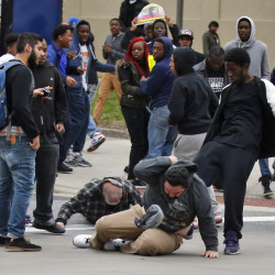 A man is kicked as he attempts to get up after being knocked down, following a march to City Hall for Freddie Gray on Saturday in Baltimore.