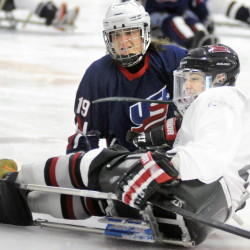 Christy Gardner, left, of the New England Warriors checks Gordie Ide, a member of the civilian team that played against Gardner's team, in a sled hockey game Sunday at the Ice Vault in Hallowell.