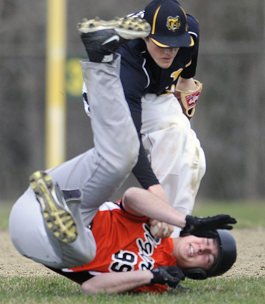 Gardiner's Logan Peacock attempts to elude a tag by Maranacook's Silas Mohlar after a run down between second and third bases Tuesday in Gardiner.