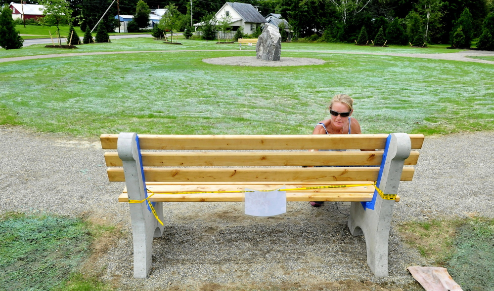 Charity Sargood paints one of the benches at Bjorn Park at the intersection on High Street and Farmington Falls Road in Farmington in August. The park will be the site of free lunches for low-income Farmington children this summer, hosted by Old South First Congregational Church.