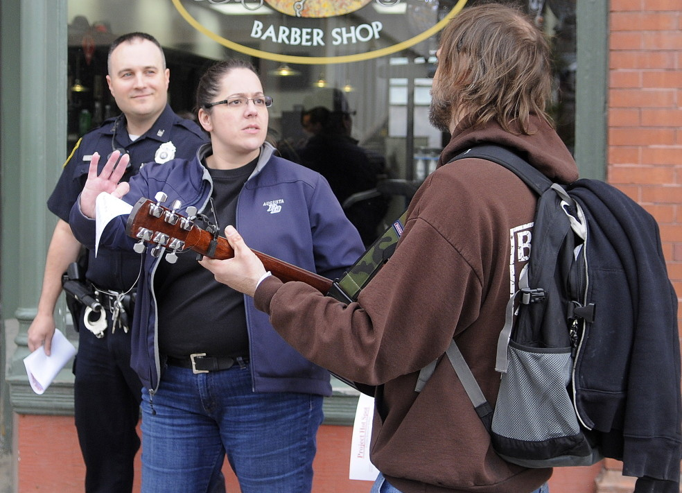 """Augusta Police Detective Tori Tracy and Officer Jesse Brann speak with a man Wednesday playing guitar on Water Street while canvassing. Law enforcement officers were notifying people of a larger police presence planned in the future in crime """"hot spots"""" while soliciting input on how to combat crime."""