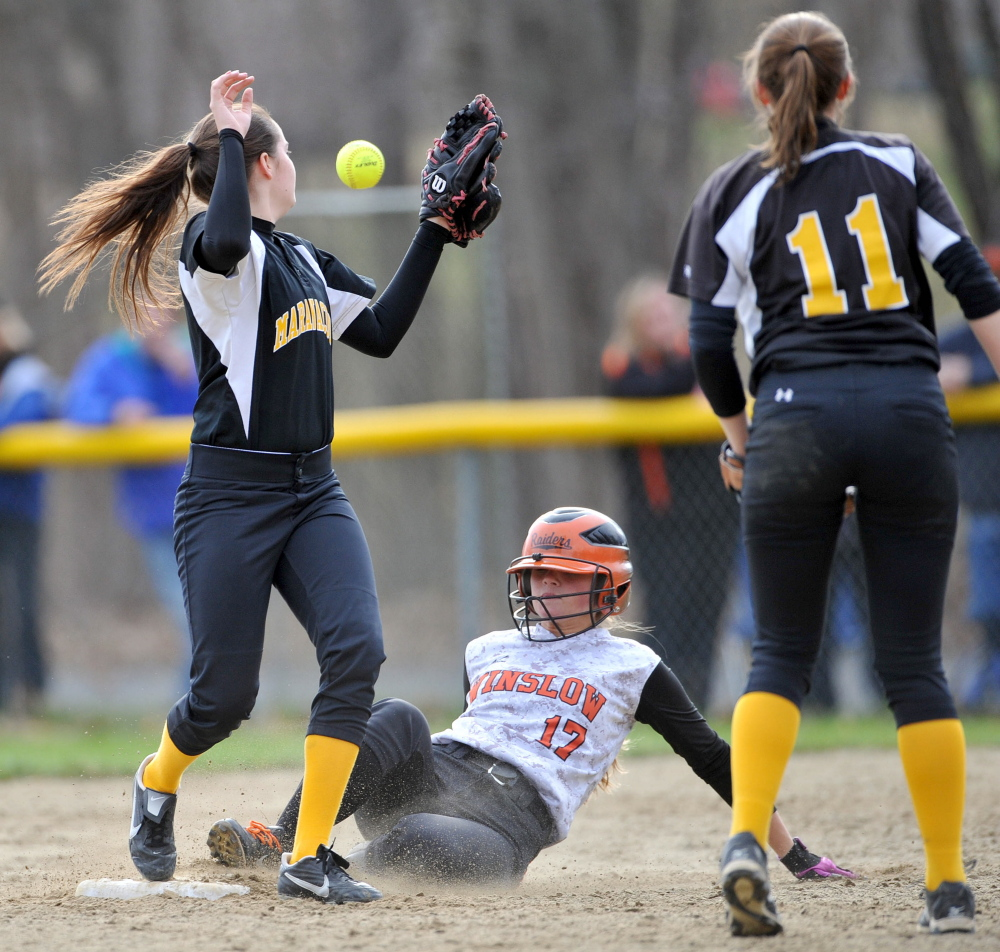 Winslow High School's Paige Veilleux, middle, slides safely into second base as Maranacook's Faith Johnson (4) tries to handle the throw during a game Wednesday in Winslow.