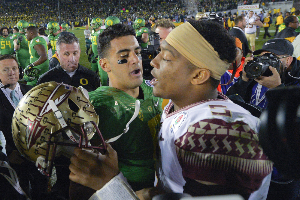 Florida State quarterback Jameis Winston, right, was selected No. 1 overall in the NFL draft to the Tampa Bay Buccaneers. The Tennessee Titans selected Oregon quarterback Marcus Mariota, left, at No. 2.